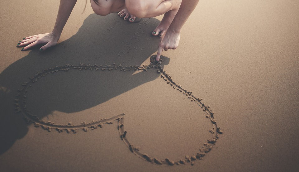 heart-drawn-in-sand-withindex-finger-loving-the-one-happy-island-ARUBA