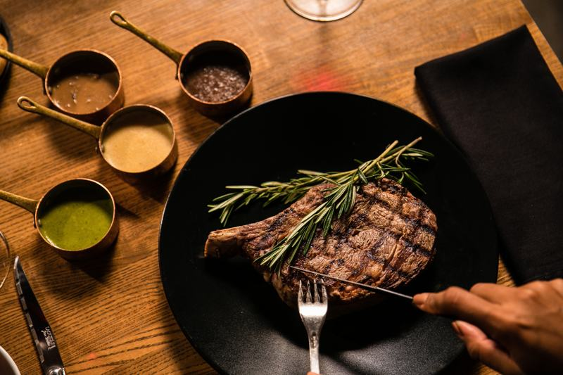 well-done-steak-on-black-plate-being-cut-with-silver-knife-and-fork-next-to-dipping-sauces