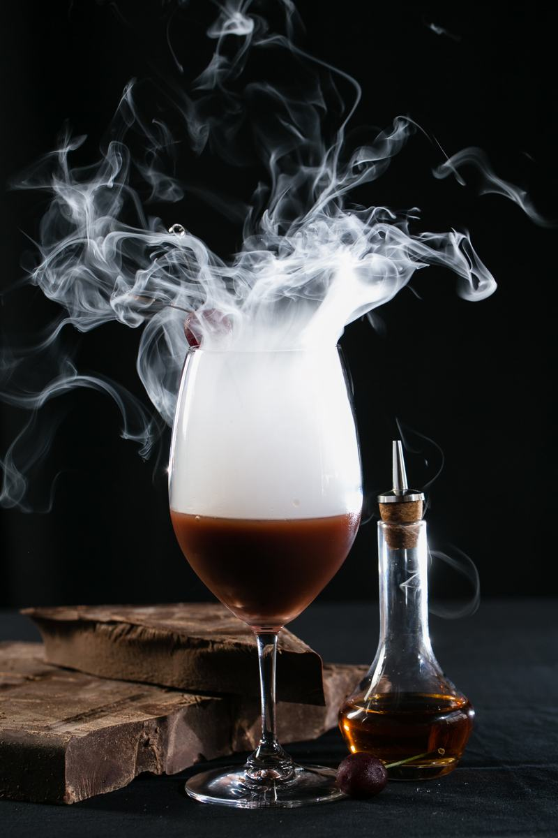 Smoked-and-misted-glass-of-red-wine-black-background
